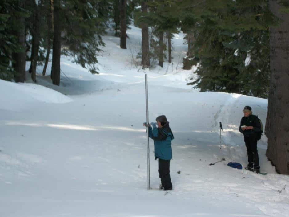 Carol Ballow and Sue Tebbe (right) measure snowpack levels at Swampy John in the Scott River drainage. (Courtesy U.S. Forest Service)