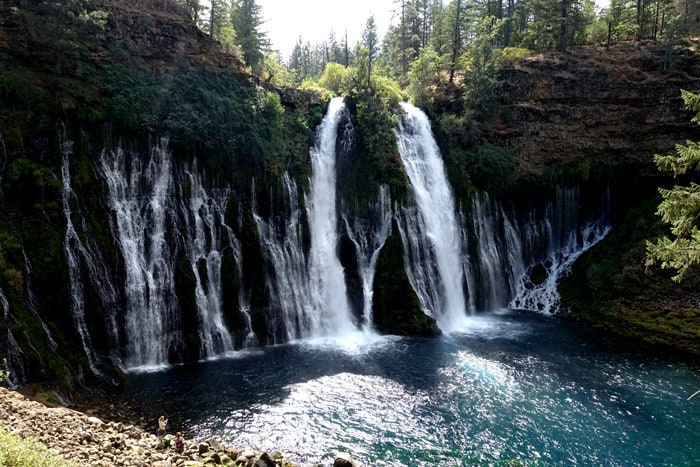 Burney Falls, fed by a huge underground reservoir, drops 100 million gallons of water daily down 129 feet to crash into a sapphire-blue pool.