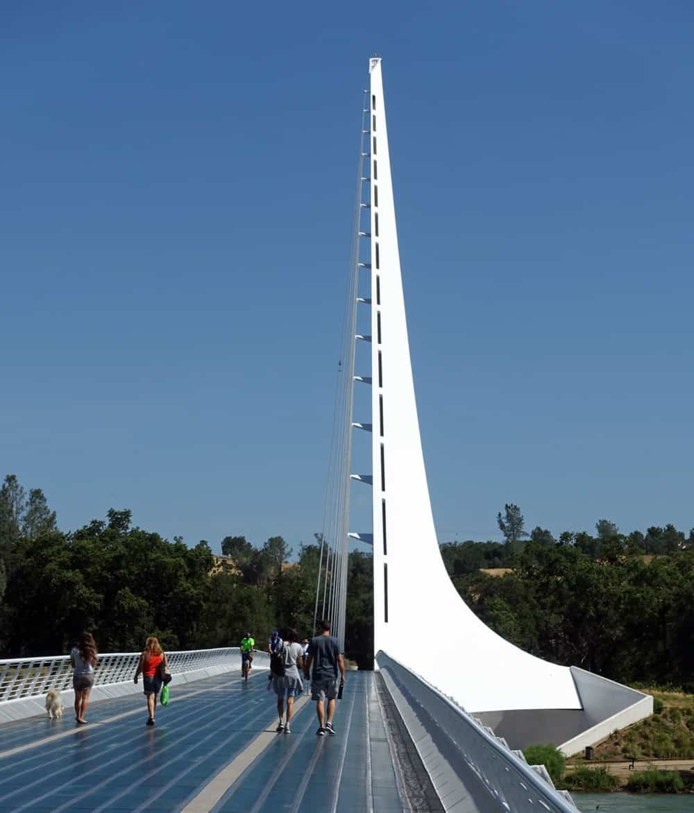Walkers crossing the Sundial Bridge at Redding's Turtle Bay, heading toward the Arboretum Loop Trail, the Sacramento River Trail, and the McConnell Arboretum and Botanical Gardens.