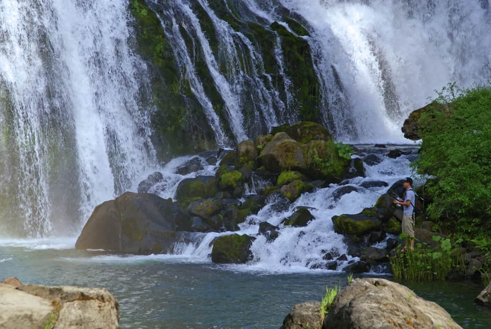 An angler tries his luck at the base of Middle McCloud Falls. Fishing is popular along the river.