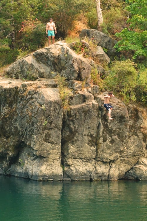 Swimmers jumping off the cliff into the Smith River, opposite Myrtle Beach
